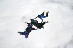 Three skydivers in freefall. With a bank of clouds beneath them Royalty Free Stock Image