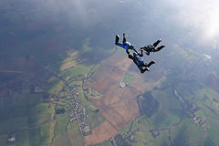 Three skydivers in freefall. With the sun lightning up the ground below Stock Image
