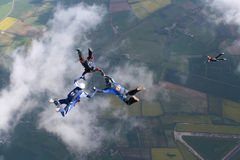Three skydivers in freefall. With a fourth below them Stock Image