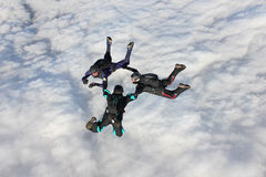 Three skydivers in freefall. Over a bank of clouds Stock Photos