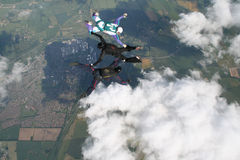 Three skydivers in freefall doing formations. Three skydivers in freefall with clouds in the background Stock Images