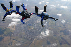 Three skydivers in a line behind each other. With a town in the background Royalty Free Stock Image