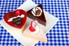 Three slice of cakes. Three slice of heart shaped cheese cake, chocolate cake, & strawberry cake Stock Photography