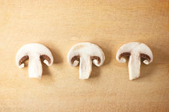 Three sliced champignons on wood cutting board Stock Photo