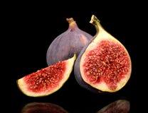 Three sliced figs  on black background Stock Photos