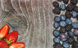 Three sliced strawberries on wood royalty free stock photos