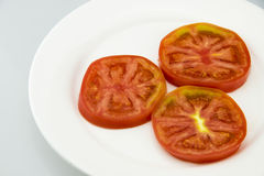 Three sliced tomatoes. White porcelain plate, put three slices tomatoes, color is very beautiful, the taste is sweet Royalty Free Stock Image