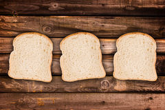 Three slices of bread, on wood planks Royalty Free Stock Photo