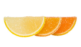 Three slices of colored marmalade  stand one behind another on a. Three slices of yellow and orange marmalade sprinkled with sugar, stand one behind another, and Stock Photo