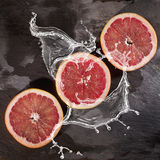 Three slices of grapefruit splashed in the water on black stone background Stock Images