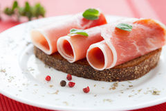Three slices of ham wrapped in a roll Royalty Free Stock Photos