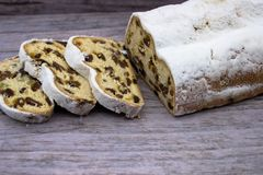 The three slices and the main part of Stollen on a wooden background. royalty free stock images