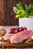 Three slices of raw pork meat on wooden plate with spices. Vertical photo of three slices of raw pork meat which are placed on dark wooden board with whole Stock Photos