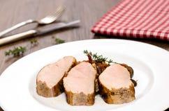 Three slices of roasted pork tenderloins Stock Photos