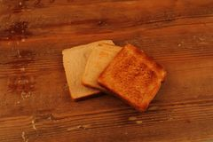 Three slices of toast on a wooden surface. Three slices of toast, each toasted for a longer time, on a wooden surface in landscape format with copy space Stock Photo