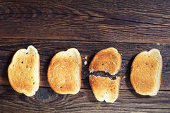 Three slices toasted bread and one ripped royalty free stock image