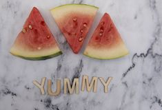 Three slices of watermelon on a marble background with the word yummy. In wooden letters Stock Images
