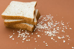 Loafs. Three slices wheat loafs with oat  on brown background Royalty Free Stock Photo