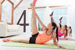 Three slim women doing stretching in gym. Achieve the split. Three young slim women doing stretching and exercising in groups while spending time in a gym Royalty Free Stock Photos