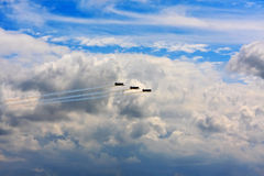 Three small airplanes. Flying above the clouds during an air show stock images