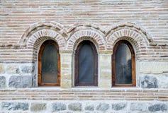 Three small arch windows on a brick wall. Closeup Stock Photos