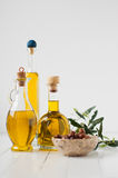 Three small bottles with olive oil and olives in brine Stock Photos