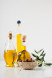 Three small bottles with olive oil and olives in brine Stock Photography