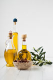Three small bottles with olive oil and olives in brine Stock Images
