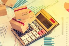 Three small boxes on a calculator. An idea of marketing Planning. And Shipping Costs  ,freight forwarding business concept. Control financial budget and service Stock Photo
