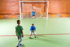 Three small boys practicing their soccer. On an indoor court lining up to try for goal Stock Photo