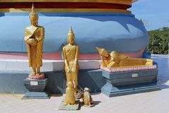 Three small Buddha statues at the base of a stupa, Samui, Thailand. Stock Photos