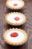Three small buns with a cherry and white icing Stock Image
