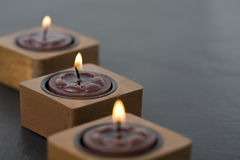 Three small candles in row Stock Photos