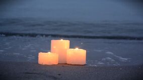 Three small candles on sandy beach near sea ocean waves burning