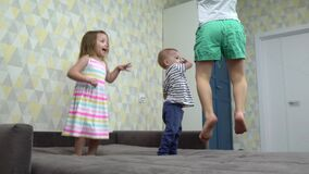 Three small children jumping on bed indoors at home, having fun.