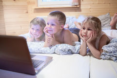 Three small children looking at laptop screen Royalty Free Stock Photos