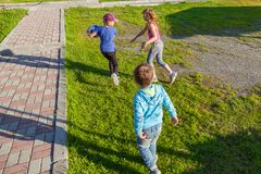 Three small children, two girls and one boy run on the green grass in the yard during the games, chasing each other to take away stock photo