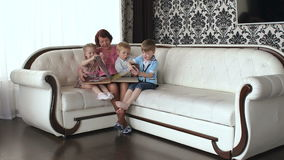 Three small children visiting her grandmother. Look at the photo album sitting on the sofa stock footage