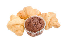 Three small croissant and chocolate muffin on a light background Stock Images