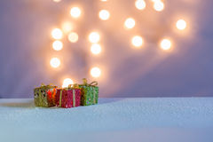 Three small gift boxes on the snow. Lights come out from red, green, and golden gift boxes on the snow with pastel colors Royalty Free Stock Photo