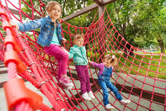 Three small girl sitting on red grid in summer Royalty Free Stock Photo