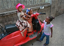 Three small girls playing near the african parked red scooter. Royalty Free Stock Images
