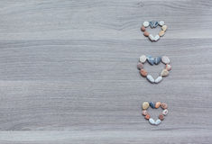 Three small hearts of multicolored pebbles on wooden surface. Ba Stock Photo