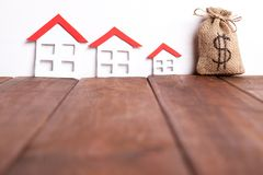 Three small houses over brown wood with a sack of money Stock Images