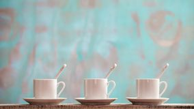 Three small porcelain cups with spoons and saucers against a rustic green background with copy space Stock Photo