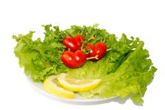 Three small red tomato cherry on the green iceberg salad and lemon slidce royalty free stock photography
