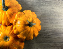 Three small ripe orange pumpkins on a natural rustic wood background with cop Royalty Free Stock Photos