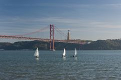 Three small sailing boats at the Tagus River with the 25 of April bridge on the background in the city of Lisbon. Portugal royalty free stock image