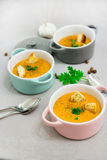 Three small serving pots or bowls with cream soup made of red lentils with rusks, spices and herbs parsley, coriander Stock Images