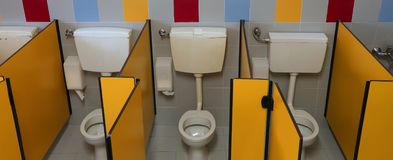 Three small toilet in the bathroom of a preschool royalty free stock image